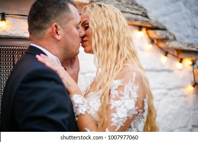 Beautiful bride and groom posing in front of old white houses with lights. close up. Alberobello