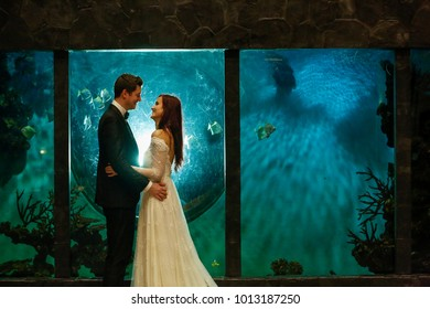 beautiful bride and groom posing in front of fish tank
