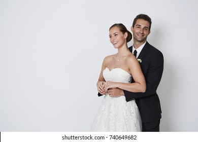 Beautiful bride and groom smiling in studio, portrait