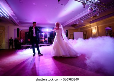 Beautiful bride and groom stand in the middle of dancefloor illuminated with pink light
