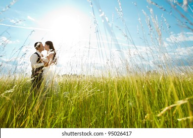 Beautiful bride and groom standing in grass and kissing. Wedding couple fashion shoot