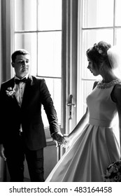 beautiful bride and groom standing together near a window
