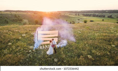 Beautiful bride and groom. Wedding ceremony in nature. Smoke bombs.Removed from the drone.