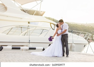 Beautiful bride and groom wedding couple near sea yacht. Happy newlywed couple at wedding. Cheerful married couple standing on the beach.