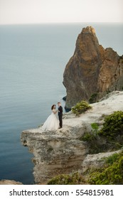 Beautiful Bride and groom wedding couple at marriage day outdoors on the mountains rock on sea background. Happy marriage couple outdoors on nature, soft sunny lights.