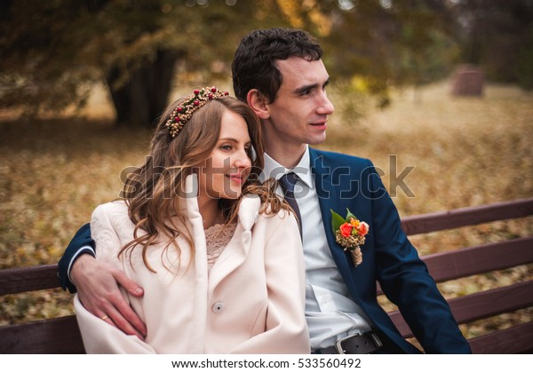 The beautiful bride and handsome groom sitting on a bench in the autumn park.