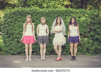 Beautiful bride and happy bridesmaids celebrating hen-party.Happy young hipster girls having fun at bridal shower, wearing colorful fluffy skirts and white t-shirt outdoors in city park on a sunny day