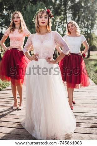 cea61bb8f3 Beautiful bride and her bridesmaids in dark pink skirts pose on the wooden  bay