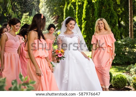 bcda0a4ff8 Beautiful bride and her friends- bridesmaids having fun and walking in park  after wedding ceremony