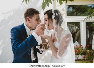 beautiful bride and her husband eat cake together