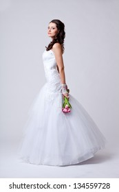 beautiful bride holding bouquet studio full length portrait and turned sideways