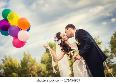 Beautiful bride holding bunch of red balloons on park. Couple of bride and groom with balloons. Newlyweds with balloons outdoors. Happy Valentines day!