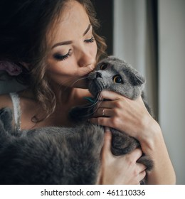 beautiful bride holding a cat by the window