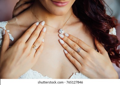 beautiful bride holding a necklace in her hands.
