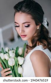 Beautiful bride holding wedding bouquet of white tulips in her hands in studio. Wediing day