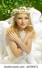 The beautiful bride lies in the field with camomiles with a wreath on a head