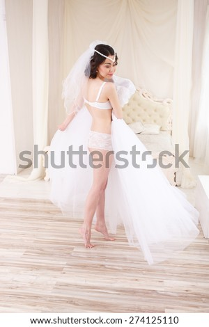 91946a6d5 Beautiful bride in lingerie trying wedding dress and dancing. Bride getting  ready on her wedding