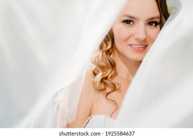 beautiful bride with long curls under the veil. delicate female portrait. Wedding make-up. Natural beauty.