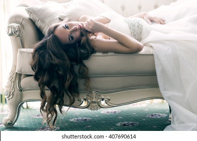 Beautiful bride with long hanging curly hair lying on the sofa in a wedding dress in a luxury room. Portrait of relaxing woman.