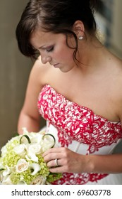 Beautiful bride looking down at her flowers