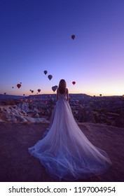 beautiful bride in a luxurious dress in the desert in the mountains against the background of flying balloons