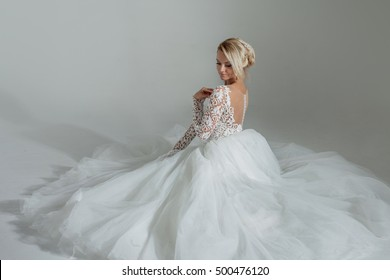 beautiful bride in luxurious wedding dress, sitting in circle long skirts. White background, top view