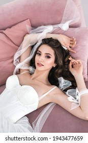 Beautiful bride is lying on a sofa in the hotel. Beauty portrait of bride