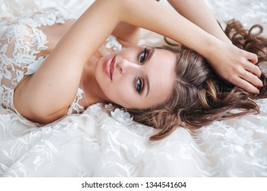 Beautiful bride is lying on a white bed in the hotel. The girl in a white dress is resting in the bedroom. Beauty portrait of bride