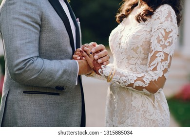 Beautiful bride with mehendi. Handsome fiance in a gray suit. Couple is holding hands