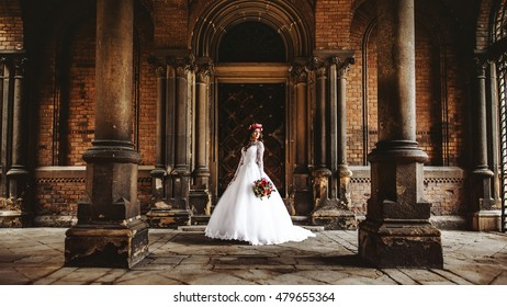 Beautiful bride near old big wooden doors