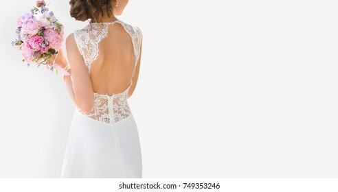 Beautiful bride on a gray background. On the woman is a long wedding dress with lace and an open back. Bouquet in hands.