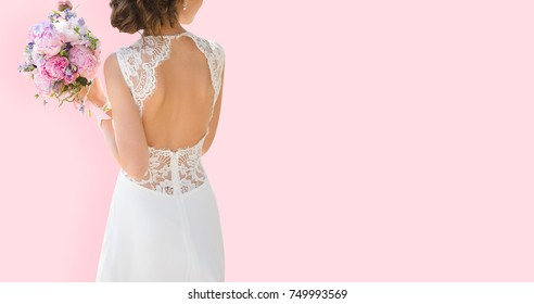 Beautiful bride on a pink background. Woman dressed in wedding dress with lace and an open back. Bouquet in hands.