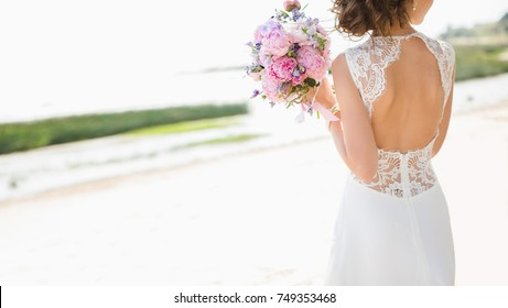 Beautiful bride on the seacoast. On the woman is a long wedding dress with lace and an open back. Bouquet in hands.