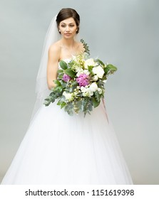 Beautiful Bride with a Pensive Expression Holding a Bouquet