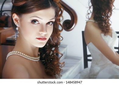 a beautiful bride with perfect make up and hairstyle sitting near the mirror