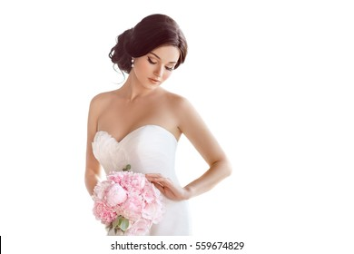 Beautiful bride perfect style. Wedding hairstyle make-up luxury wedding dress and bride's bouquet. Young attractive multi-racial Asian Caucasian model like a bride isolated on white background looking