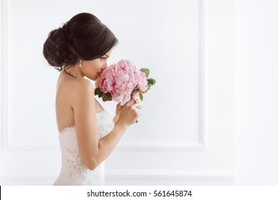 Beautiful bride perfect style. Wedding hairstyle make-up luxury wedding dress and bride's bouquet. Young attractive multi-racial Asian Caucasian model like a bride against white room smells at bouquet