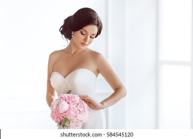 Beautiful bride perfect style. Wedding hairstyle make-up luxury wedding dress and bride's bouquet. Young attractive multi-racial Asian Caucasian model like a bride against white room at studio looking