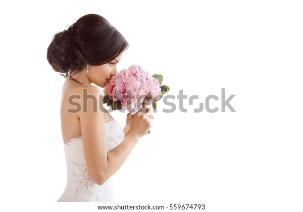 Beautiful bride perfect style. Wedding hairstyle make-up luxury wedding dress and bride's bouquet. Young attractive multi-racial Asian Caucasian model like a bride isolated on white background smells