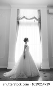 Beautiful bride portrait in wedding dress near window