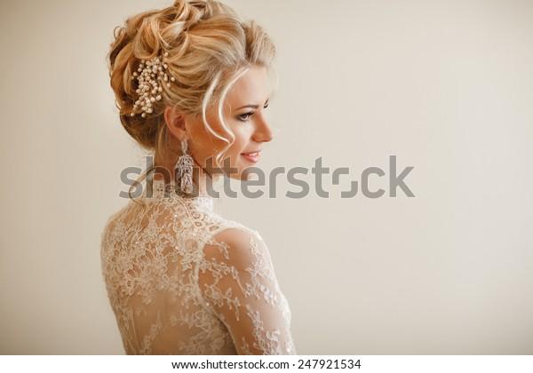 Schöne Bride Portrait Hochzeit Make-up Frisur, wunderschöne junge Frau in weißem Kleid zu Hause. Serie.