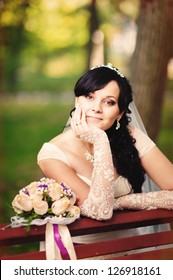 Beautiful bride posing with a flowers in her wedding day  in a park. wedding dress. Bridal wedding bouquet of flowers