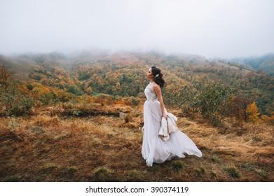 Beautiful bride posing in high mountain scenery
