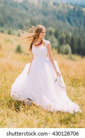 Beautiful bride posing on the golden autumn field with astonishing mountain landscape behind her
