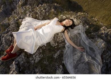 Beautiful bride posing on rocks