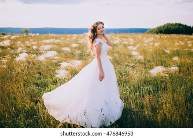 Beautiful bride posing on sunny grass field