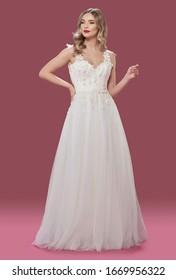 Beautiful bride posing in wedding dress in  photo studio isolated