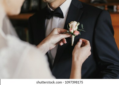 beautiful bride putting on stylish simple boutonniere with roses on groom black suit. wedding morning preparations