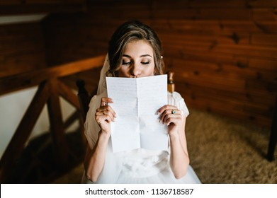 Beautiful bride reading, kissing letter from the groom for love. Bride's tears of happiness, joy. The bride sits at window and reads letter to groom. Wedding vows. Morning of the bride.