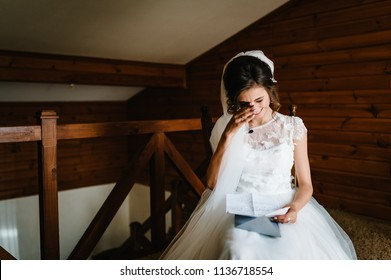 Beautiful bride reading letter from the groom for love. Bride's tears of happiness, joy. The bride sits at window and reads letter to groom. Wedding vows. Morning of the bride. Dress with lace.